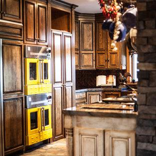 Esempio di una grande cucina rustica con lavello a tripla vasca, ante con bugna sagomata, top in granito, paraspruzzi a effetto metallico, paraspruzzi con piastrelle di metallo, elettrodomestici da incasso, pavimento in mattoni e isola