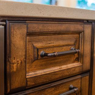 他の地域の中くらいのラスティックスタイルのおしゃれなキッチン (アンダーカウンターシンク、レイズドパネル扉のキャビネット、ヴィンテージ仕上げキャビネット、クオーツストーンカウンター、ベージュキッチンパネル、木材のキッチンパネル、シルバーの調理設備、淡色無垢フローリング、ベージュの床、ベージュのキッチンカウンター) の写真