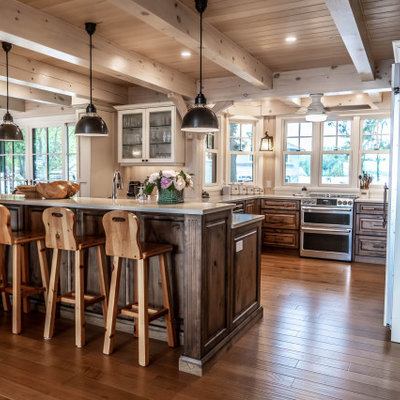 Example of a mid-sized mountain style u-shaped light wood floor and beige floor eat-in kitchen design in Other with an undermount sink, raised-panel cabinets, distressed cabinets, quartz countertops, beige backsplash, wood backsplash, stainless steel appliances, an island and beige countertops