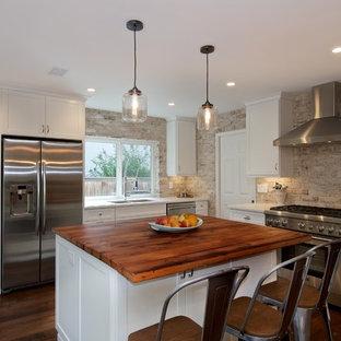 サンディエゴの中くらいのラスティックスタイルのおしゃれなキッチン (アンダーカウンターシンク、シェーカースタイル扉のキャビネット、白いキャビネット、クオーツストーンカウンター、白いキッチンパネル、シルバーの調理設備、濃色無垢フローリング、レンガのキッチンパネル) の写真