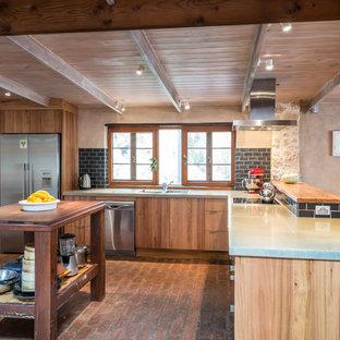 Rustik inredning av ett mellanstort kök, med en dubbel diskho, släta luckor, skåp i mellenmörkt trä, bänkskiva i betong, svart stänkskydd, stänkskydd i tunnelbanekakel, rostfria vitvaror, tegelgolv och en köksö