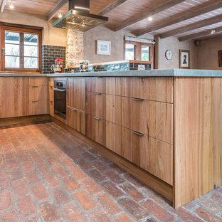 Foto på ett mellanstort rustikt kök, med en dubbel diskho, släta luckor, skåp i mellenmörkt trä, bänkskiva i betong, svart stänkskydd, stänkskydd i tunnelbanekakel, rostfria vitvaror, tegelgolv och en köksö