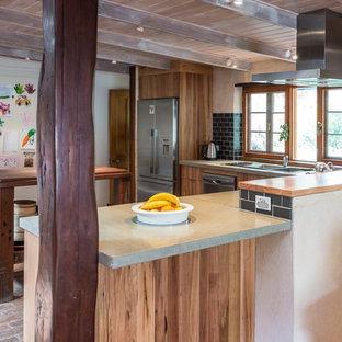Inspiration for a mid-sized country l-shaped eat-in kitchen in Adelaide with a double-bowl sink, flat-panel cabinets, medium wood cabinets, concrete benchtops, black splashback, subway tile splashback, stainless steel appliances, brick floors and with island.