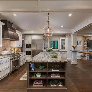 デトロイトの広いトランジショナルスタイルのおしゃれなキッチン (エプロンフロントシンク、白いキャビネット、御影石カウンター、グレーのキッチンパネル、レンガのキッチンパネル、シルバーの調理設備、無垢フローリング、マルチカラーのキッチンカウンター) の写真