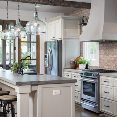 Mid-sized mountain style galley medium tone wood floor open concept kitchen photo in Birmingham with a farmhouse sink, shaker cabinets, white cabinets, concrete countertops, red backsplash, stainless steel appliances and an island