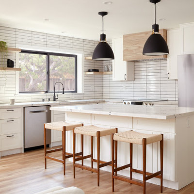Inspiration for a transitional l-shaped medium tone wood floor and brown floor open concept kitchen remodel in San Francisco with an undermount sink, shaker cabinets, white cabinets, white backsplash, stainless steel appliances, an island and white countertops