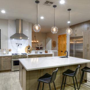 フェニックスのサンタフェスタイルのおしゃれなキッチン (アンダーカウンターシンク、シェーカースタイル扉のキャビネット、中間色木目調キャビネット、シルバーの調理設備、グレーの床、白いキッチンカウンター) の写真