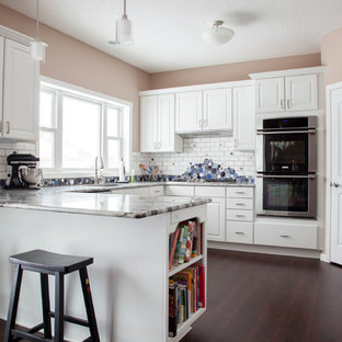 Design ideas for a large transitional u-shaped eat-in kitchen in Minneapolis with an undermount sink, louvered cabinets, white cabinets, granite benchtops, multi-coloured splashback, ceramic splashback, stainless steel appliances, dark hardwood floors, a peninsula and brown floor.