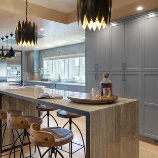Große Moderne Wohnküche in L-Form mit Landhausspüle, Schrankfronten mit vertiefter Füllung, Edelstahl-Arbeitsplatte, Küchengeräten aus Edelstahl, hellem Holzboden, zwei Kücheninseln, grauen Schränken, Küchenrückwand in Grau, braunem Boden und grauer Arbeitsplatte in Sonstige