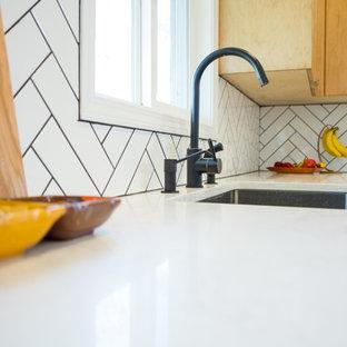 アトランタの大きいコンテンポラリースタイルのおしゃれなキッチン (ドロップインシンク、フラットパネル扉のキャビネット、淡色木目調キャビネット、珪岩カウンター、白いキッチンパネル、磁器タイルのキッチンパネル、シルバーの調理設備、セラミックタイルの床、黒い床) の写真
