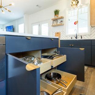 アトランタの大きい北欧スタイルのおしゃれなキッチン (ドロップインシンク、フラットパネル扉のキャビネット、淡色木目調キャビネット、珪岩カウンター、白いキッチンパネル、磁器タイルのキッチンパネル、シルバーの調理設備、セラミックタイルの床、黒い床) の写真