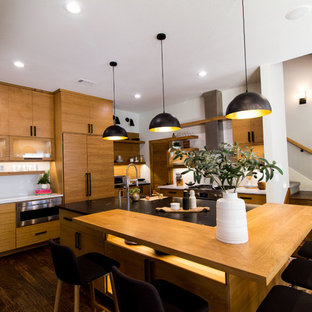 Large danish dark wood floor and brown floor eat-in kitchen photo in Dallas with flat-panel cabinets, light wood cabinets, granite countertops, white backsplash, subway tile backsplash, stainless steel appliances, an island and black countertops