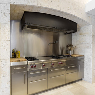 Example of a large minimalist single-wall porcelain floor eat-in kitchen design in New York with metallic backsplash, metal backsplash, an undermount sink, flat-panel cabinets, medium tone wood cabinets, granite countertops, stainless steel appliances and an island