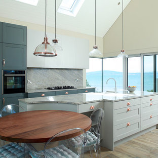 This is an example of a medium sized coastal kitchen in London with shaker cabinets, marble worktops, grey splashback, marble splashback, stainless steel appliances, an island, grey worktops, a belfast sink, blue cabinets, light hardwood flooring and brown floors.