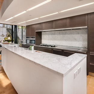 Contemporary eat-in kitchen ideas - Example of a trendy galley medium tone wood floor and brown floor eat-in kitchen design in Seattle with an undermount sink, flat-panel cabinets, dark wood cabinets, white backsplash, stainless steel appliances, an island and white countertops