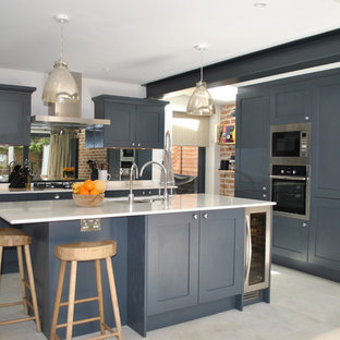 Medium sized contemporary l-shaped kitchen in London with a double-bowl sink, recessed-panel cabinets, blue cabinets, quartz worktops, mirror splashback, stainless steel appliances, an island, grey floors and white worktops.