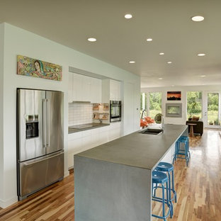 Contemporary open concept kitchen photos - Inspiration for a contemporary galley medium tone wood floor open concept kitchen remodel in Kansas City with a double-bowl sink, flat-panel cabinets, white cabinets, concrete countertops, white backsplash, stainless steel appliances and an island