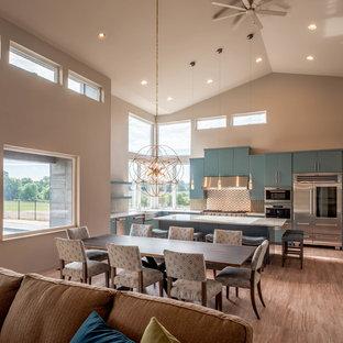 他の地域の広いモダンスタイルのおしゃれなキッチン (エプロンフロントシンク、フラットパネル扉のキャビネット、ターコイズのキャビネット、珪岩カウンター、緑のキッチンパネル、サブウェイタイルのキッチンパネル、シルバーの調理設備、コルクフローリング、ベージュの床) の写真
