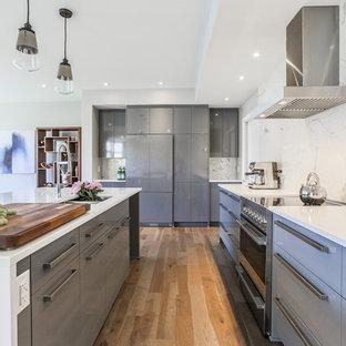 Exemple d'une cuisine tendance avec un évier encastré, un placard à porte plane, des portes de placard grises, une crédence blanche, un électroménager en acier inoxydable, un sol en bois brun et un îlot central.