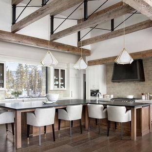 Idee per una cucina a L rustica con lavello sottopiano, ante in stile shaker, ante bianche, paraspruzzi grigio, elettrodomestici in acciaio inossidabile, pavimento in legno massello medio, isola, pavimento marrone e top bianco