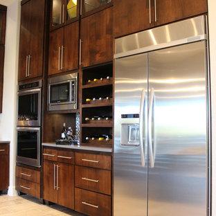 オースティンの広いモダンスタイルのおしゃれなキッチン (アンダーカウンターシンク、フラットパネル扉のキャビネット、濃色木目調キャビネット、クオーツストーンカウンター、マルチカラーのキッチンパネル、モザイクタイルのキッチンパネル、シルバーの調理設備、セラミックタイルの床) の写真