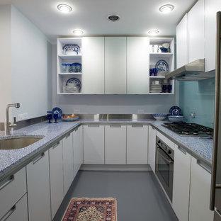 Idéer för att renovera ett avskilt, litet funkis u-kök, med en undermonterad diskho, släta luckor, vita skåp, bänkskiva i återvunnet glas, blått stänkskydd, glaspanel som stänkskydd, rostfria vitvaror, betonggolv och en halv köksö