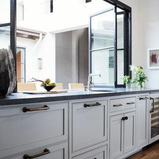 Medelhavsstil inredning av ett mellanstort beige beige kök, med en enkel diskho, flerfärgad stänkskydd, stänkskydd i keramik, integrerade vitvaror, mellanmörkt trägolv, en köksö och brunt golv