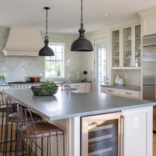 Large country eat-in kitchen in DC Metro with a farmhouse sink, concrete benchtops, blue splashback, glass tile splashback, light hardwood floors, with island, grey benchtop, recessed-panel cabinets, beige cabinets, stainless steel appliances and beige floor.