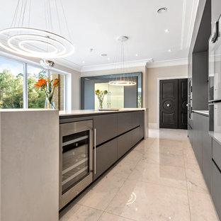 バークシャーのモダンスタイルのおしゃれなキッチン (フラットパネル扉のキャビネット、グレーのキャビネット、ミラータイルのキッチンパネル、大理石の床、白い床) の写真