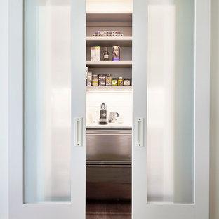 Bild på ett stort funkis kök, med en dubbel diskho, luckor med glaspanel, vita skåp, bänkskiva i täljsten, flerfärgad stänkskydd, stänkskydd i marmor, rostfria vitvaror, mellanmörkt trägolv, en köksö och beiget golv
