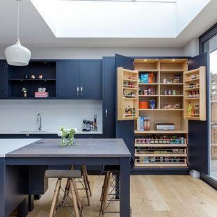 Inredning av ett klassiskt stort blå blått kök, med en enkel diskho, bänkskiva i glas, mellanmörkt trägolv, brunt golv, blå skåp, vitt stänkskydd, en köksö och släta luckor