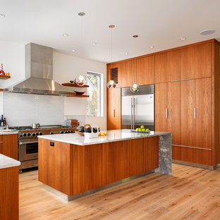 Example of a large minimalist u-shaped light wood floor and beige floor open concept kitchen design in Vancouver with flat-panel cabinets, medium tone wood cabinets, white backsplash, glass tile backsplash, stainless steel appliances, an island and quartzite countertops