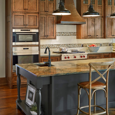 Inspiration for a timeless dark wood floor kitchen remodel in Dallas with recessed-panel cabinets, medium tone wood cabinets, white backsplash, stainless steel appliances and an island