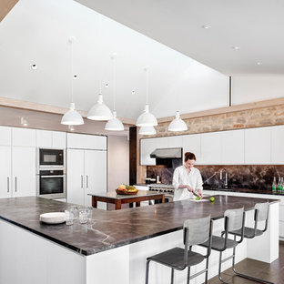 Modern eat-in kitchen inspiration - Example of a minimalist l-shaped dark wood floor and brown floor eat-in kitchen design in Austin with white cabinets, gray backsplash, an island and gray countertops