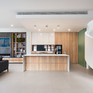 Design ideas for a contemporary l-shaped open plan kitchen in Melbourne with flat-panel cabinets, medium wood cabinets, black appliances, an island, grey floor and white benchtop.