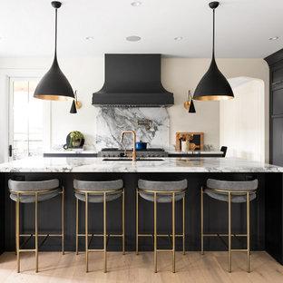 バンクーバーの広いトランジショナルスタイルのおしゃれなキッチン (アンダーカウンターシンク、落し込みパネル扉のキャビネット、黒いキャビネット、大理石カウンター、白いキッチンパネル、御影石のキッチンパネル、黒い調理設備、淡色無垢フローリング、茶色い床、白いキッチンカウンター) の写真