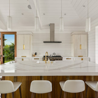 Inspiration for a large beach style galley open plan kitchen in Hawaii with a farmhouse sink, flat-panel cabinets, white cabinets, quartz benchtops, white splashback, stone slab splashback, stainless steel appliances, porcelain floors, with island and grey floor.