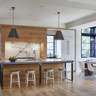 Contemporary eat-in kitchen ideas - Trendy galley light wood floor eat-in kitchen photo in Minneapolis with an undermount sink, flat-panel cabinets, white cabinets, white backsplash, an island, solid surface countertops, stone slab backsplash and paneled appliances