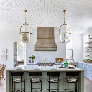 Foto på ett maritimt vit kök, med skåp i shakerstil, blå skåp, vitt stänkskydd, rostfria vitvaror, mellanmörkt trägolv och en köksö