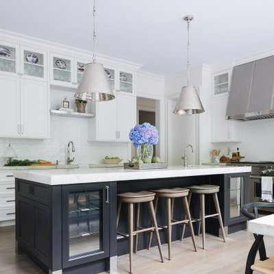 Transitional medium tone wood floor eat-in kitchen photo in Chicago with white cabinets, white backsplash, ceramic backsplash, stainless steel appliances, an island and white countertops