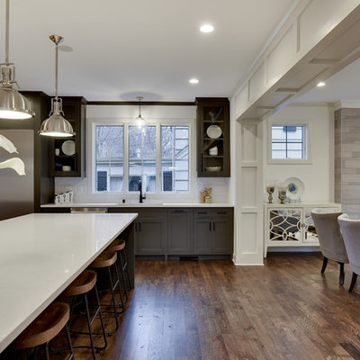 Example of a large transitional l-shaped dark wood floor and brown floor eat-in kitchen design in Minneapolis with an undermount sink, shaker cabinets, gray cabinets, white backsplash, stainless steel appliances and an island