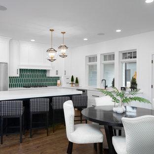 他の地域の中くらいのトランジショナルスタイルのおしゃれなキッチン (シングルシンク、白いキャビネット、緑のキッチンパネル、セラミックタイルのキッチンパネル、シルバーの調理設備、白いキッチンカウンター、シェーカースタイル扉のキャビネット、人工大理石カウンター、無垢フローリング、青い床) の写真
