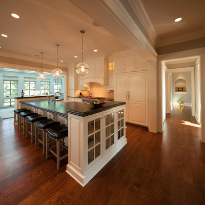 Inspiration for a transitional galley kitchen remodel in Minneapolis with a farmhouse sink, raised-panel cabinets, white cabinets and paneled appliances