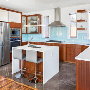 Design ideas for a mid-sized contemporary u-shaped open plan kitchen in Other with blue splashback, with island, an undermount sink, flat-panel cabinets, medium wood cabinets, solid surface benchtops, ceramic splashback, stainless steel appliances, marble floors, grey floor and white benchtop.
