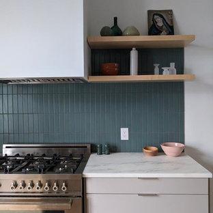 ボストンの大きいヴィクトリアン調のおしゃれなキッチン (ドロップインシンク、フラットパネル扉のキャビネット、グレーのキャビネット、大理石カウンター、青いキッチンパネル、セラミックタイルのキッチンパネル、シルバーの調理設備の、淡色無垢フローリング、ベージュの床、白いキッチンカウンター) の写真