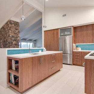Inspiration for a large midcentury u-shaped open plan kitchen in San Diego with an undermount sink, flat-panel cabinets, dark wood cabinets, blue splashback, glass sheet splashback, stainless steel appliances, porcelain floors and multiple islands.