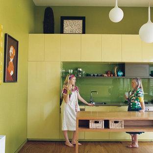 Inspiration för ett mellanstort funkis kök, med en enkel diskho, släta luckor, gröna skåp, träbänkskiva, grönt stänkskydd, glaspanel som stänkskydd, integrerade vitvaror, plywoodgolv och en köksö
