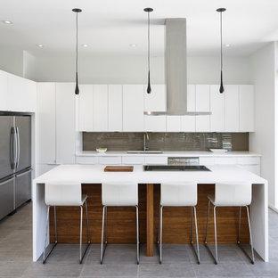 Идея дизайна: угловая кухня-гостиная среднего размера в современном стиле с врезной раковиной, плоскими фасадами, белыми фасадами, серым фартуком, техникой из нержавеющей стали, островом, фартуком из стеклянной плитки, столешницей из акрилового камня и бетонным полом