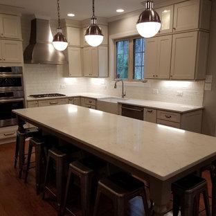ローリーの中サイズのモダンスタイルのおしゃれなキッチン (アンダーカウンターシンク、レイズドパネル扉のキャビネット、茶色いキャビネット、御影石カウンター、ベージュキッチンパネル、トラバーチンの床、黒い調理設備) の写真