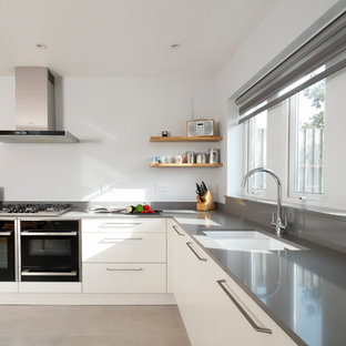 This is an example of a small contemporary l-shaped kitchen in Cardiff with flat-panel cabinets, white cabinets, quartz worktops, porcelain flooring, grey floors, grey worktops, a submerged sink, black appliances and grey splashback.